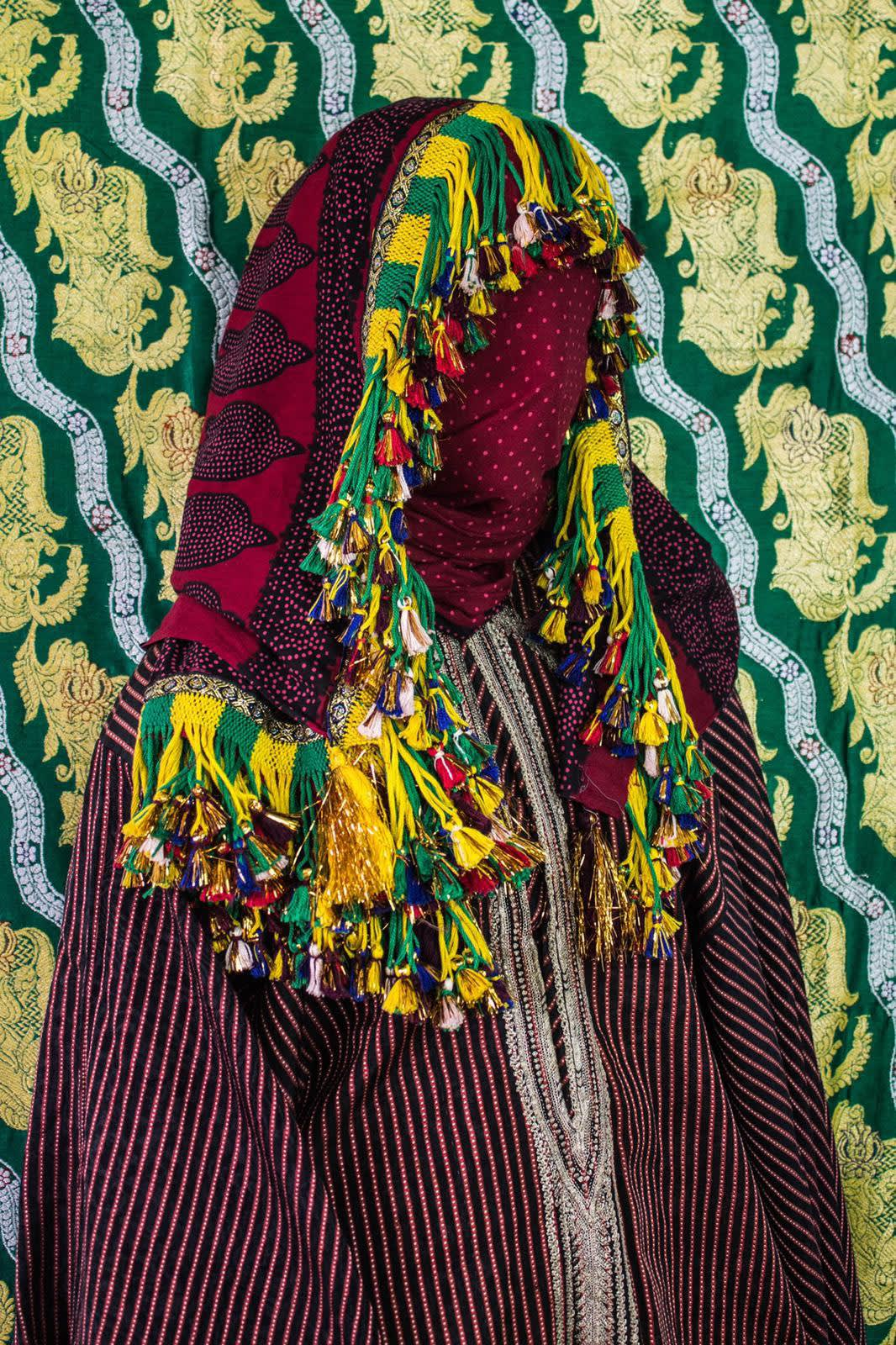 Kadia, BORDERLAND series, by Alia Ali. 2017. A model is draped in colorful fabric and tassels which completely obscures their form, photographed against a pattered fabric background