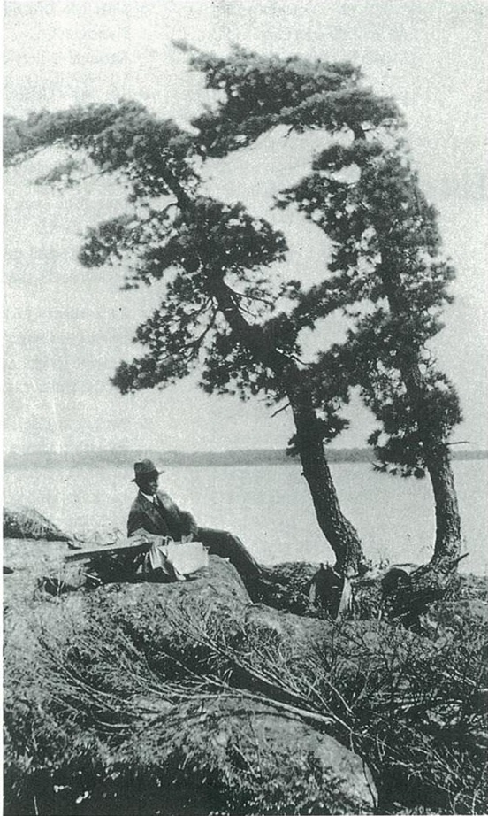 J.E.H. MacDonald sketching under the shade of a poplar tree during his trip to Sturgeon Bay in 1931.