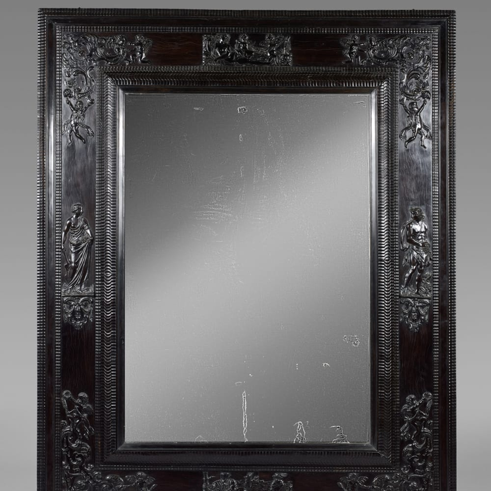 Important mirror with bevelled mercury in a large ebony frame with low-relief decorations depicting the theme of Love, Northern France, end of 17th century