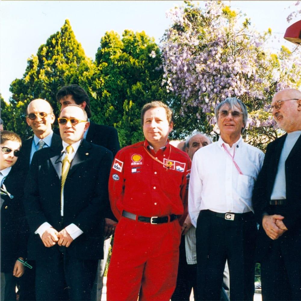 © Maggiore g.a.m. | Franco Calarota, Jean Todt, Bernie Eccleston, Arman, Piero Ferrari and Raffaello de Brasi at the vernissage of Rampante by Arman, Imola, 1999.