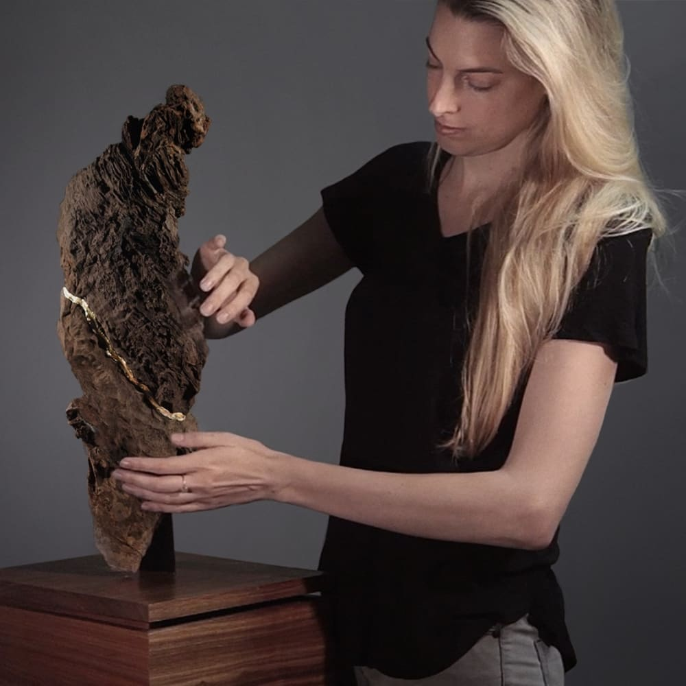 "Jenna Burchell interacting with S25°58'47.2548"" E27°46'32.1672"" Songsmith (Cradle of Humankind) l 2016 l Kiaat, resin, copper alloy, speaker & circuit l 80x32x32cm"