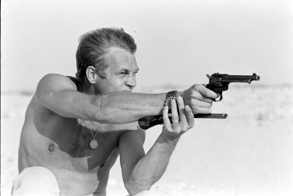 John Dominis, Steve McQueen aiming a pistol in the desert, CA, 1963