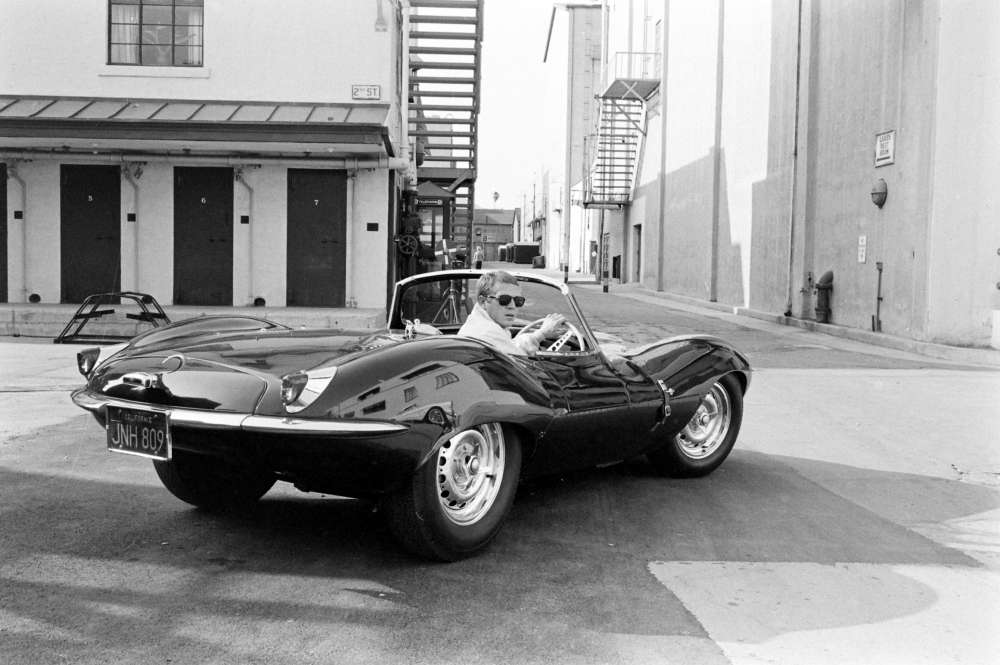John Dominis, Steve McQueen in black jaguar at studio, CA, 1963