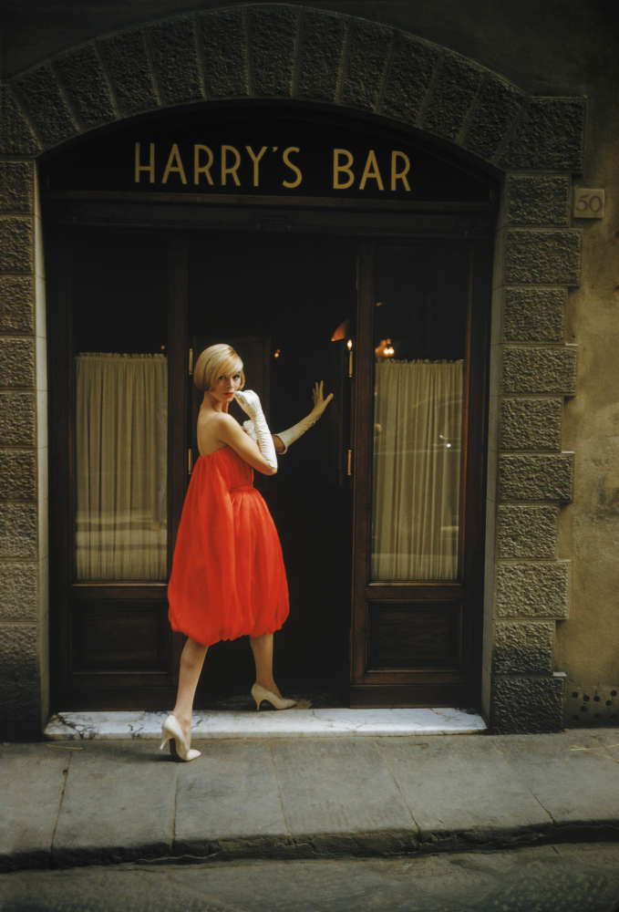 """Mark Shaw, A model wearing a Fabiani """"Bag"""" dress is photographed outside Harry's Bar in Florence, Italy in Via del Parione, 1957"""