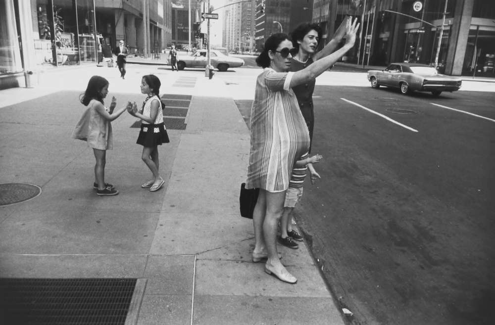 Garry Winogrand, New York, (two women hailing cab, one is pregnant; and two children playing pattycakes), from Women are better than men. Not only have they survived, they do prevail portfolio, 1968