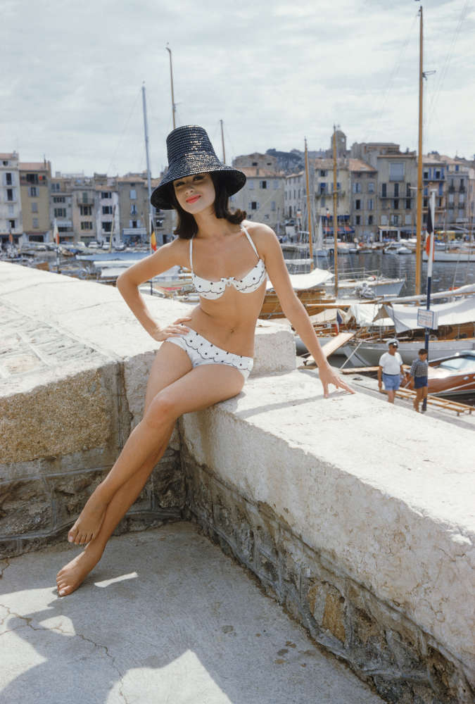 Mark Shaw, Photographed for the January 1961 issue of LIFE, Christine Mayer poses on the jetty overlooking St. Tropez harbor wearing the year's biggest Riviera hit, an embroidered organdy bikini designed by Andejo of Nice, 1961