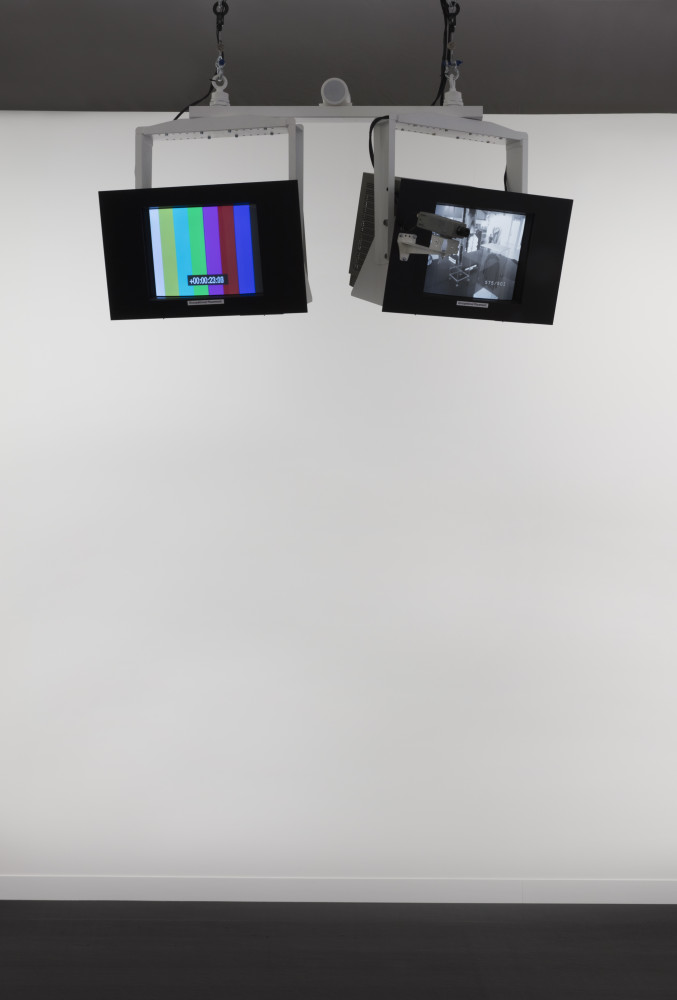 Julia Scher Occupational Placement, 1989-90 Monitors, hanging system, monitor brackets, monitor masks, surveillance camera, camera bracket, video switcher, media players, SD cards, cables and connectors, loudspeaker with infrared motion sensor 10-channel digital video (color and black and white, silent) and real-time video stream (black and white, silent), sound installation Installation dimensions and time-based media components duration variable