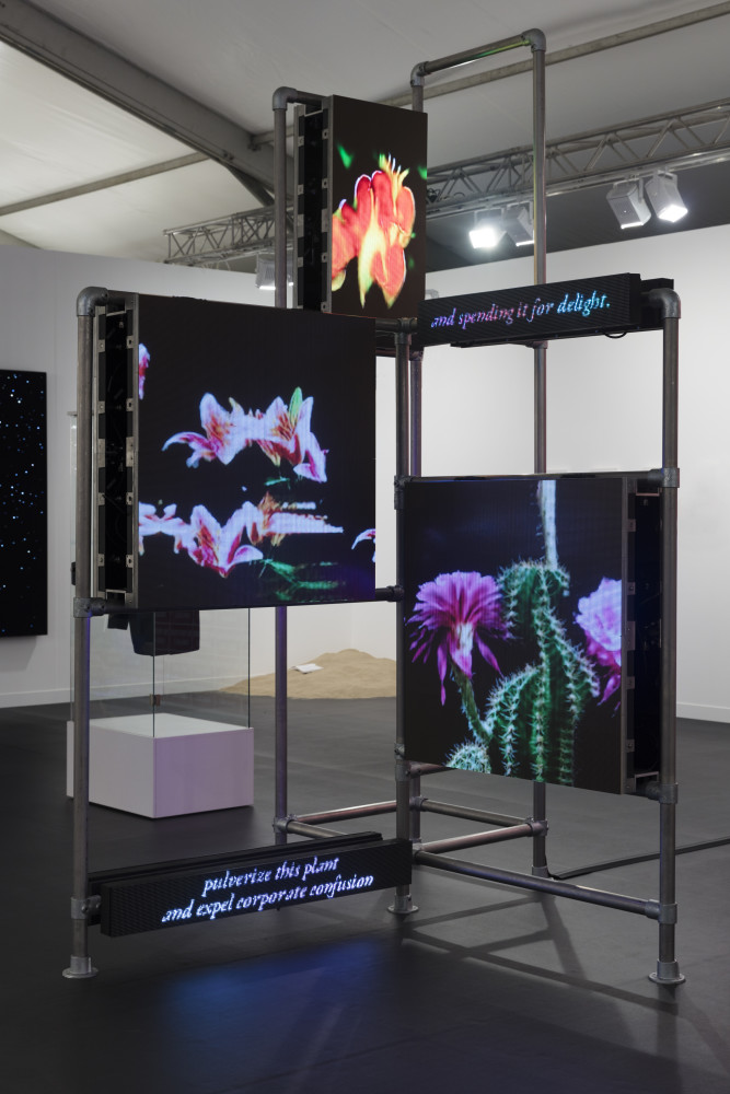 Hito Steyerl Power Plants, 2019 Stainless steel scaffolding structures, LED panels (3,9 mm pitch), multichannel video loop (color, silent), moving text lines 3 parts: 335 x 216 x 210 cm (131 7/8 x 85 1/8 x 82 5/8 in) 330,6 x 184,1 x 218 cm (129 7/8 x 72 1/2 x 85 7/8 in) 365 x 331,1 x 272,6 cm (143 3/4 x 130 1/4 x 107 1/8 in) Installation dimensions variable
