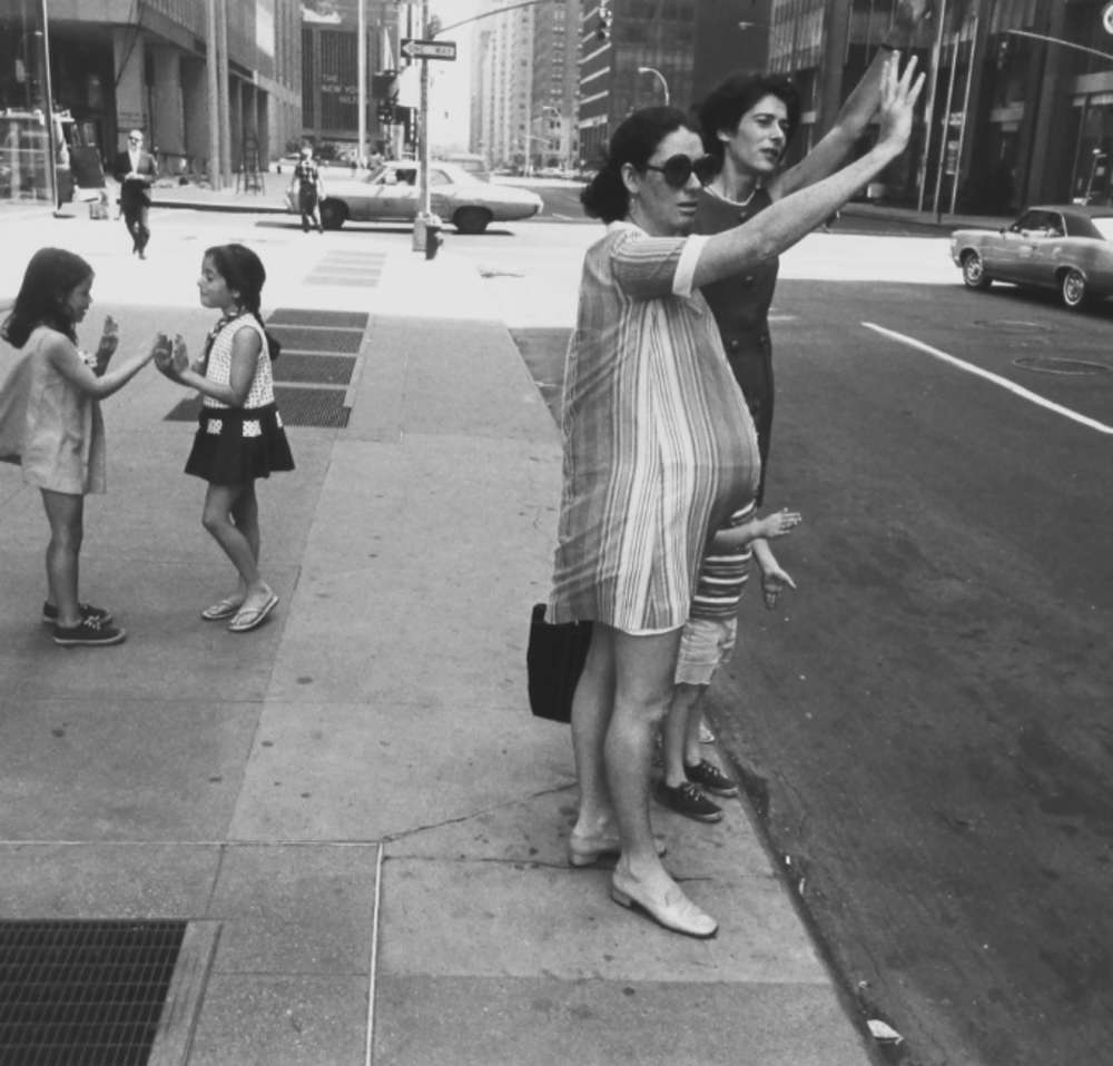 Garry Winogrand - New York, (two women hailing cab, one is pregnant; and two children playing pattycakes), from Women are better than men. Not only have they survived, they do prevail portfolio
