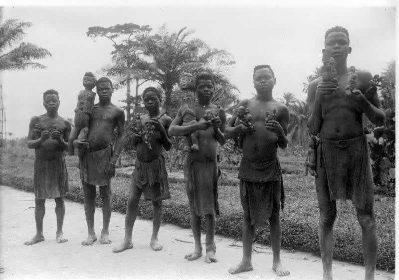 Young Bwende men on their way to the missionary station of Kingyi to give in their 'minkisi' power statues in order to convert to Christianity. Photographed by Edvard Karlman in 1912. Collection Statens museer för världskultur – Etnografiska museet, Stockholm (0177.0025).
