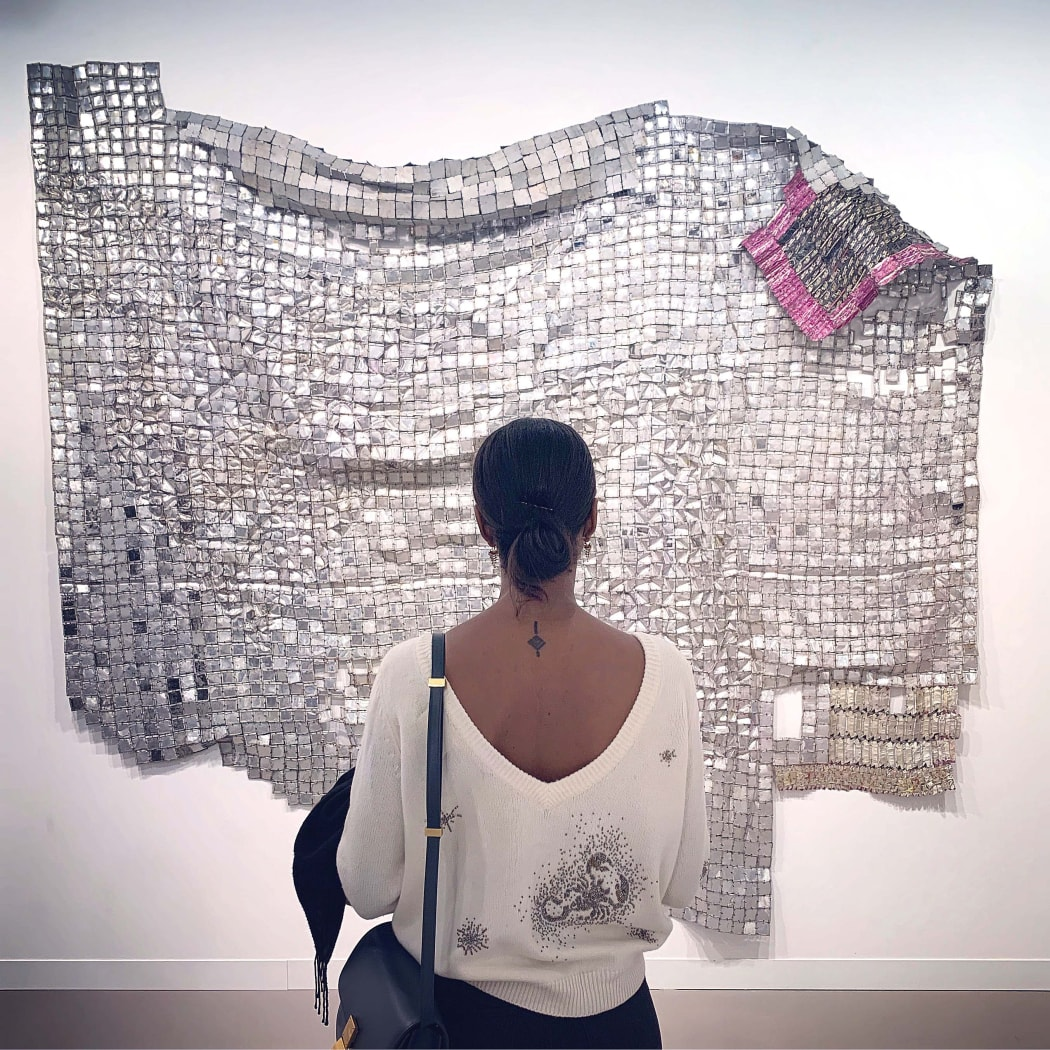 Dana Endundo Ferreira looking at artwork sculpture installation from Ghanaian artist El Anatsui at Frieze art fair london 2019. buy African contemporary and modern art online artists discover information education exhibition art diaspora