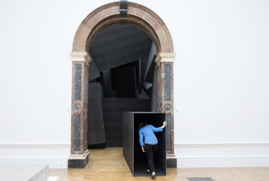 A visitor enters Antony Gormley's Cave (2019) at the Royal Academy of Arts. © the Artist. Photo: David Parry.