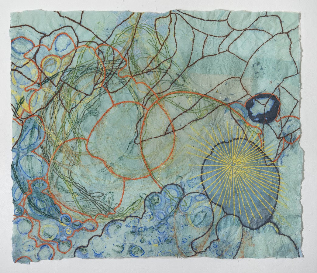 """Nancy Cohen's """"Dissoulution"""" done with paper pulp and handmade paper in various shades of green, blue, orange, yellow and brown. The piece depicts several design layers on the light aqua paper. These designs are overlapping each other creating depth."""