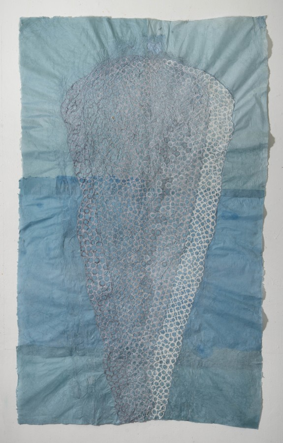 """Nancy Cohen's """"re: Precaurious"""" done with paper pulp and handmade paper in various shades of gray, white and blue. The piece depicts two layers of paper pulp the blue paper. These designs are overlapping each other creating depth."""