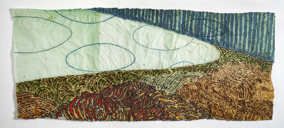 """Nancy Cohen's """"Underside"""" created using paper pulp, ink and handmade paper in shades of green, blue, brown and red. The work consists of four separate layers overlapping each other creating an illusion of depth. Each layer has a separate design pattern."""