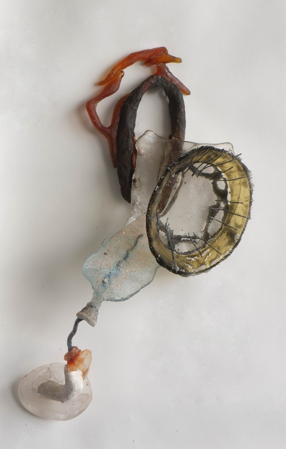 """Nancy Cohen's """"Issue"""" art piece made out of glass, metal and ceramic. The medium used are colored in shades of yellow, orange, blue, clear, brown and black. Pieces of glass are layered on top of each other attached to a metal wire on a small clear stand."""