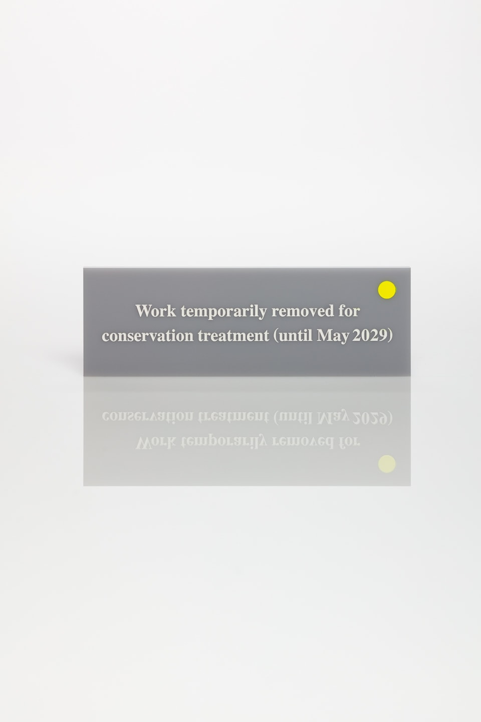Anna Blessmann and Peter Saville Work temporarily removed for conservation treatment (until May 2029), 2015 Perspex Grey 9981. Text etched and infilled in white with fluorescent yellow 809C dot. Accompanied by a signed certificate. 15 x 5 x 0.5 cm Edition of 20