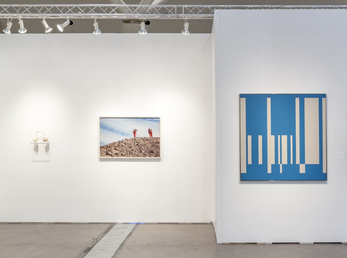 Art fair booth with three artworks. From left to right: shell headphones, a photograph of two MDRS scientists, and an abstract blue painting.