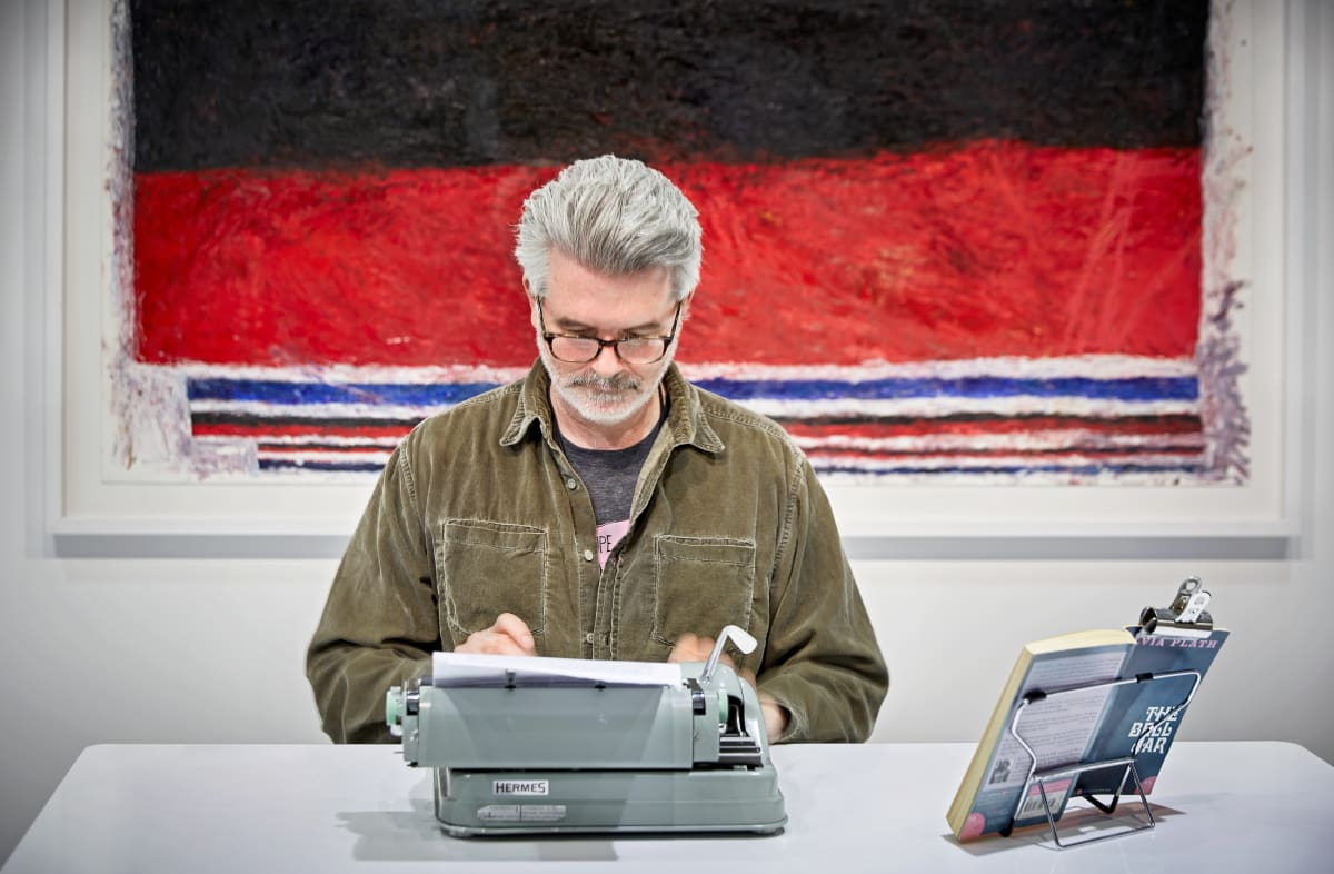 Tim Youd sits at a desk typing The Bell Jar in front of artworks in the booth