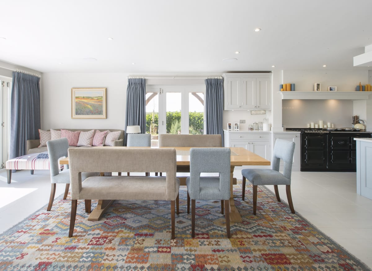 A painting by local artist Edward Noott is the backdrop in this Cotswolds open plan kitchen & dining room