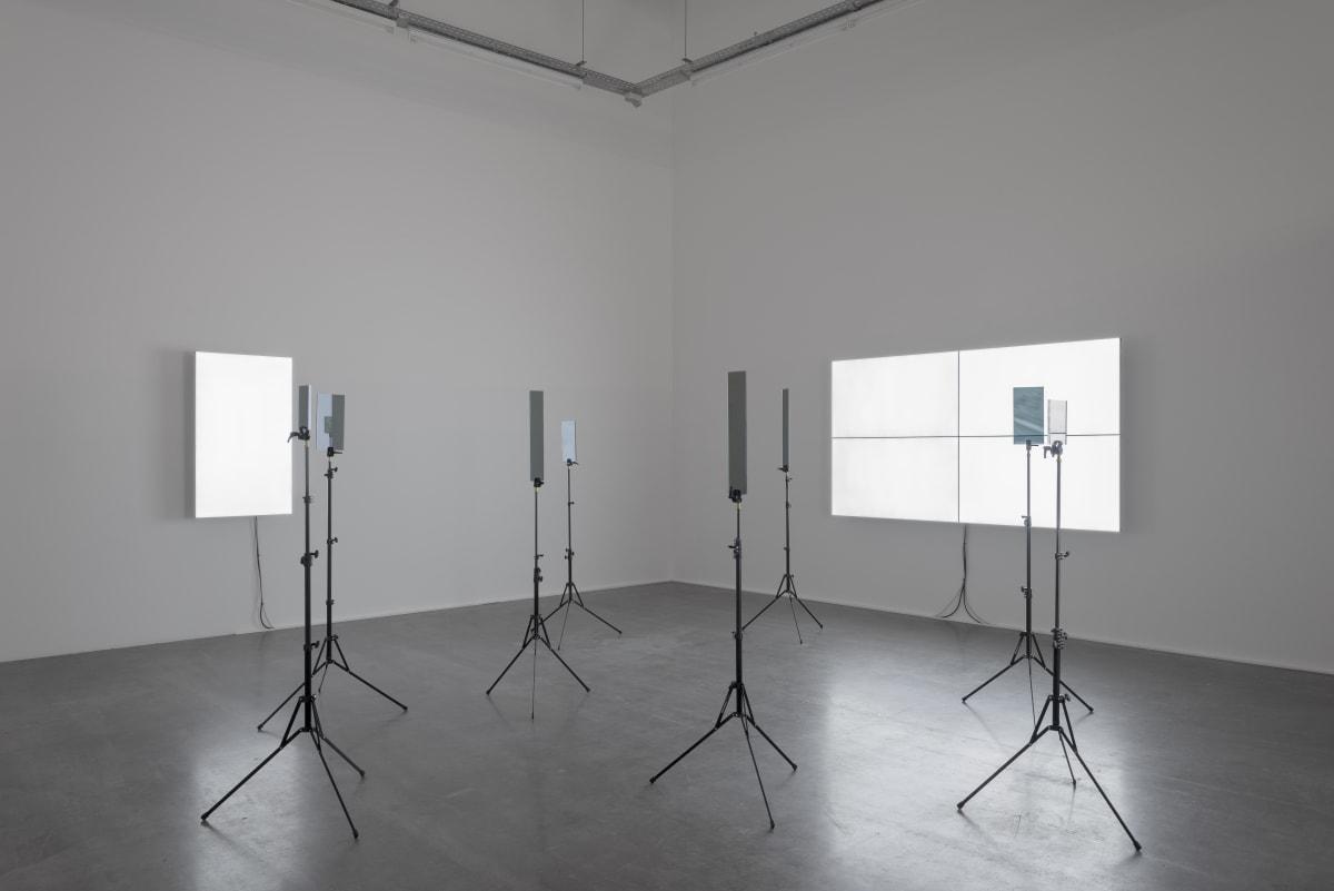 Emmanuel Van der Auwera, VideoSculpture XX (The World's 6th Sense), 2019, 4 x 46 inch LCD screens, 2 x 55 inch LCD screens, 10 x tripods with custom plexiglass, HD video variable, Install view Open Skies at Wiels - Contemporary art centre, Photo by Hugard