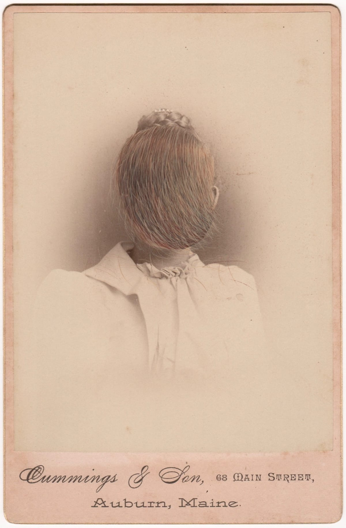 Vintage painting in shades of tan and black. The painting depicts a portrait of a woman whose face is covered by strokes of hair. The may challenge the viewer's perspective into believing if it is the woman's rear view.