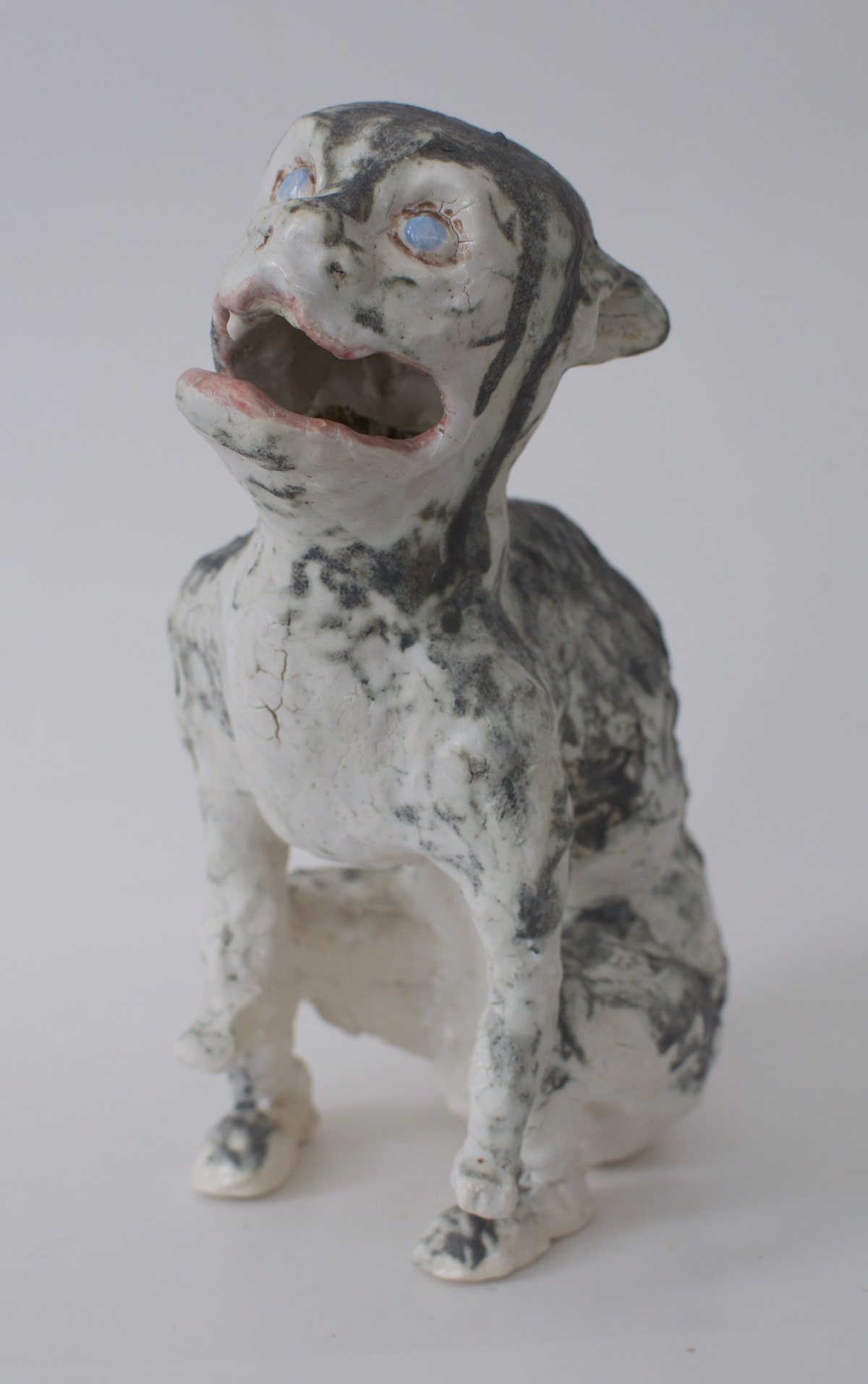 """Mary Carlson's """"Dog Demon"""" made with glazed stoneware in gray, blue and pink color. The sculpture resembles an unusual looking dog barking hence its """"demon"""" name."""