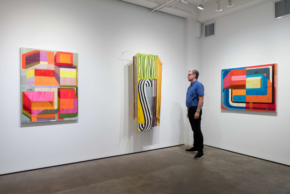 """Installation shot of three works by Deborah Zlotsky. A visitor is looking at """"Bandwidth"""" made from vintage scarves. The other two works """"Detours and delays"""" (left) and """"Sunshine Patriot"""" (right) are oil paintings on canvas."""