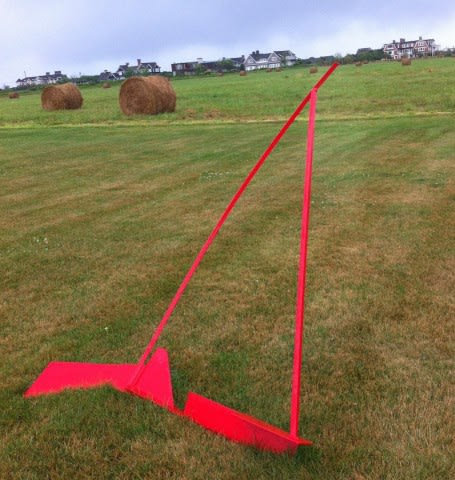 This is a photograph of an art piece that is sitting on a field with the flat surface having an angle. The art piece's placement as well as having a bright red color makes it stand out compared to the houses and hay rolls in the distance.