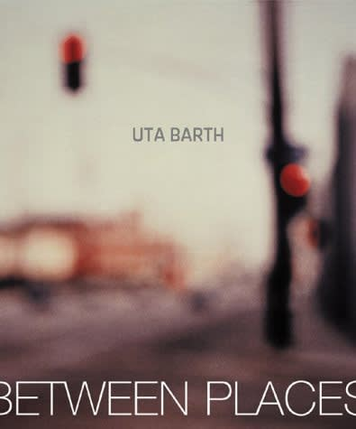 """Exhibition catalogue cover for Uta Barth exhibition """"in between places"""". Blurred photo of a traffic light hanging over a street corner. Grey text: Uta Barth, between places"""