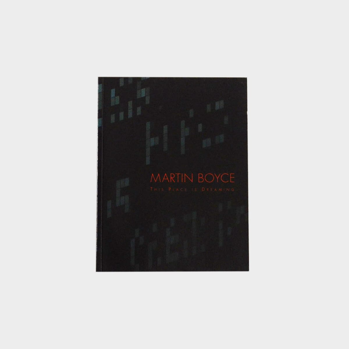 "Martin Boyce exhibition catalogue cover. Red text reads ""Martin Boyce: This Place is Dreaming"" on a black background with illegible digital sign letters in a dark blue-gray."