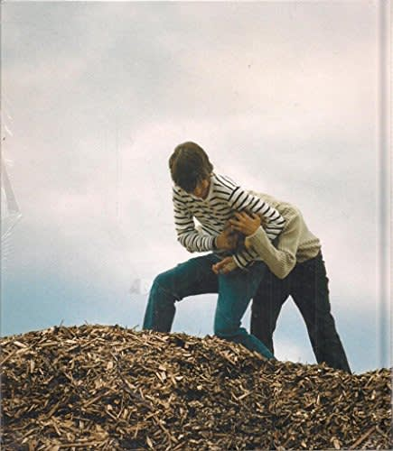 "Exhibition catalogue cover for Phill Collins exhibition ""Yeah, you, baby you"". Two boys tussle on top of a pile of woodchips. Boy wearing a striped sweater has the other in a headlock."