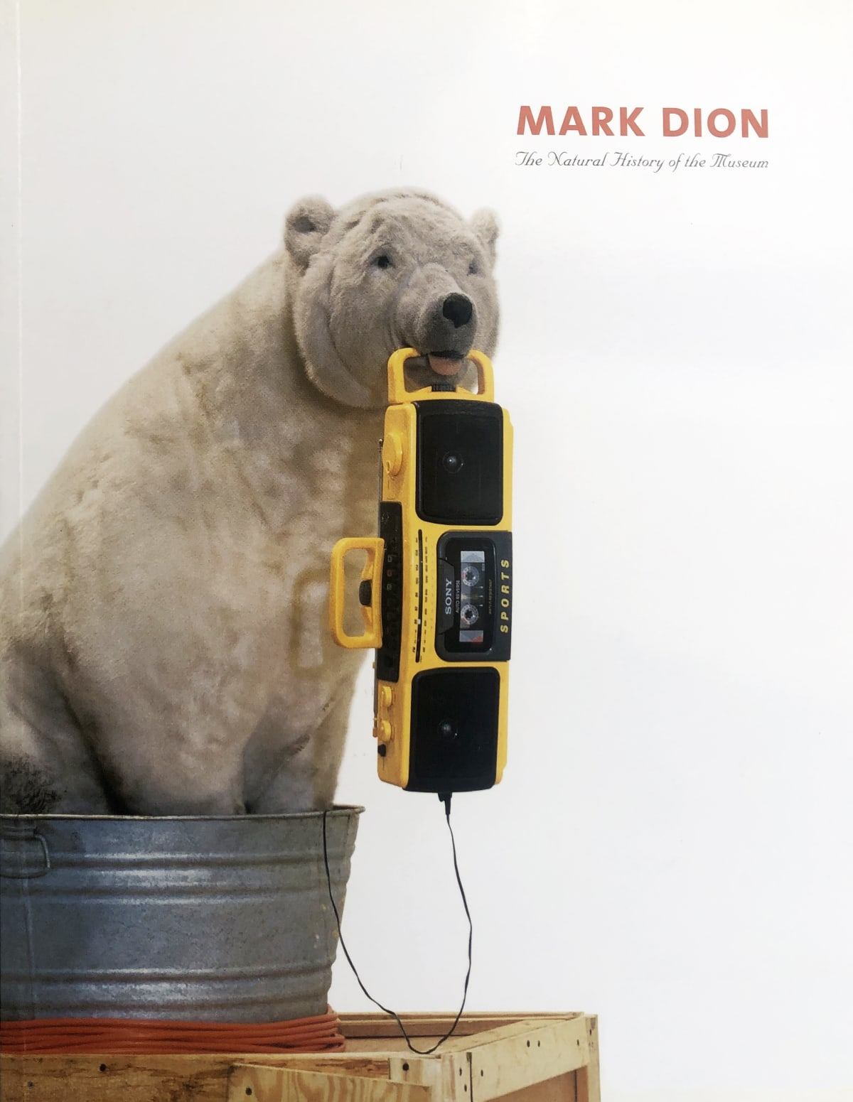 "Exhibition catalogue cover for Mark Dion exhibition. Photo of a toy stuffed polar bear sitting in a tin bucket and holding a boom box in its mouth. Title text: ""Mark Dion, The Natural History of the Museum"""