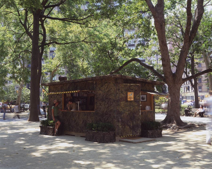 Installation image of the artwork in the park. A square camouflage stand under trees. A person leans out a window to talk to a person wearing shorts learning against the roofed structure.