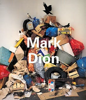 "Exhibition catalogue cover. Photo of a tall ile of cardboard boxes, plastic bags, tires, taxidermied birds and other trash in a corner. White title text: ""Mark Dion"""