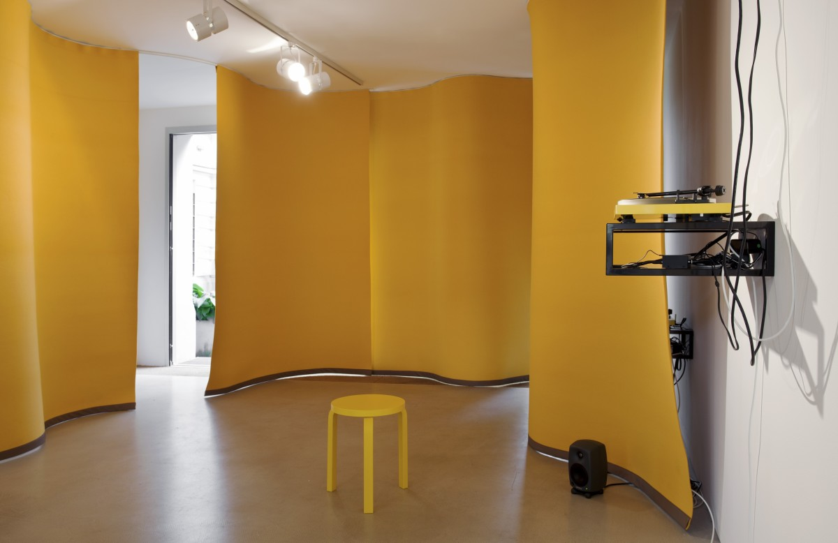 Angela Bulloch Yellow Music Station – Extra Large, 2012 Six yellow felt curtains, yellow Alvar Aalto Stool, wall mounted table, sound system, wall mount 180 cm width each, 6 part (curtain) Installation dimensions variable