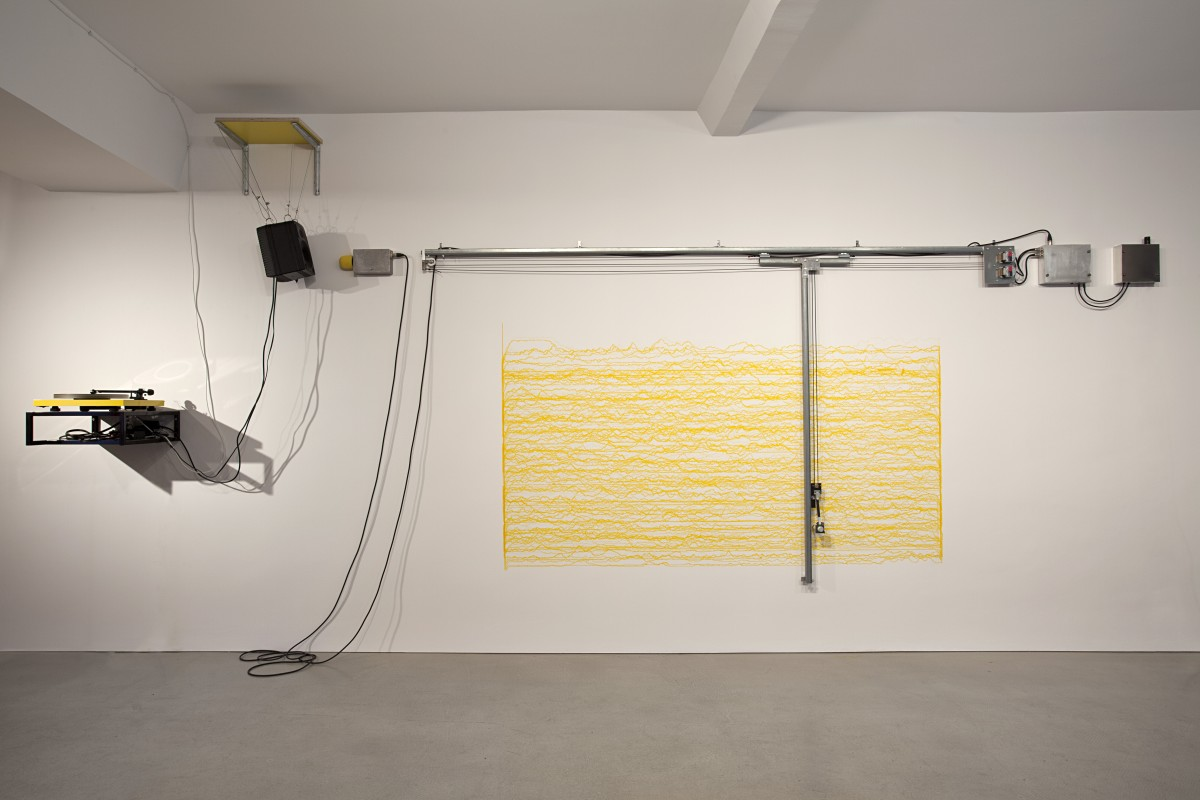 "Angela Bulloch, Short Big Yellow Drawing Machine, 2012, Drawing Machine, ink (yellow), wall mounted table, MP3 player or yellow record player, ABCDLP 002 record, pre amp, various cables, Genelec speaker, sound piece ""Short Big Drama for YDM"" by George van Dam, dimensions variable, Collection of the National Gallery of Victoria, Melbourne. Photo © Andrea Rossetti"