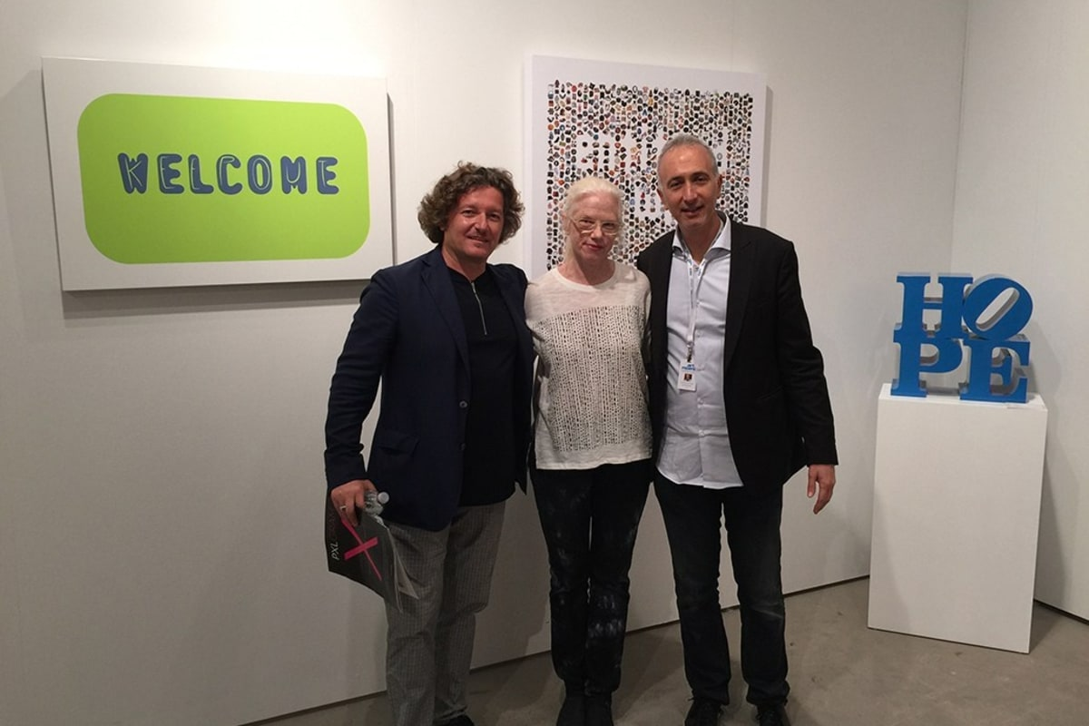 "Helidon Xhixha, Nancy Dwyer and Howard Rosenbaum in front of ""Welcome"" and ""Entitled to What"" by Nancy Dwyer and ""HOPE (Blue/White)"" by Robert Indiana."