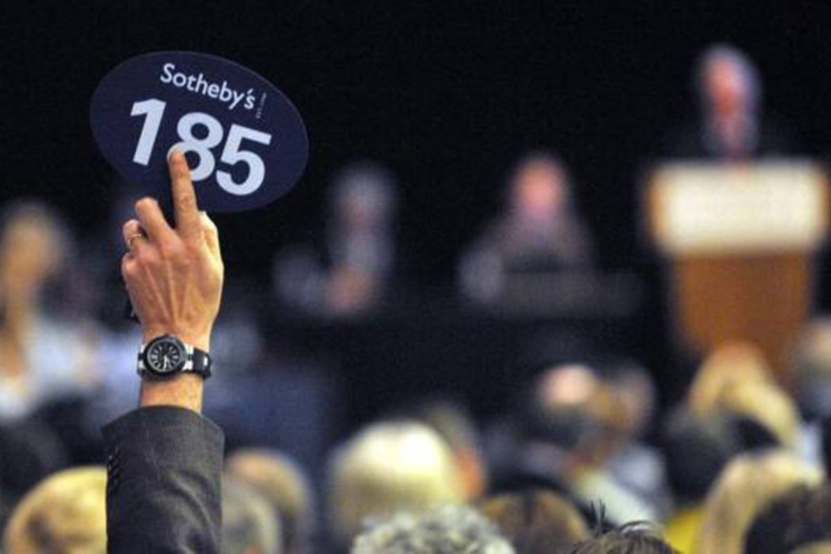 Photograph of a Sotheby's auction in Canada with the focus on someone holding a sign reading the number 185.