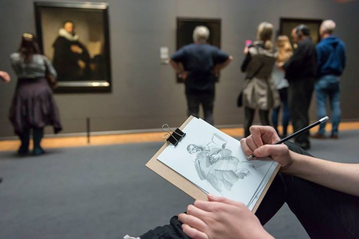 Photograph of a person doing a study sketch while other museum visitors are in the background out of focus.