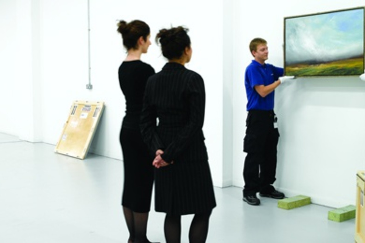 Photograph of two men installing a painting on a wall at an art gallery. Two women observe as it is installed.