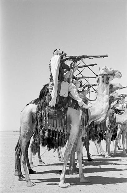 """George Rodger, Desert Patrol. Desert Patrol on manoeuvres in the desert at Al-Mafraq. The Camel Corps were the original """"Glubb's Girls"""". Recruited from Bedouin Arabs, they wore their hair in long ringlets, wore long-skirted robes and darkened their eyes with khol, 1952."""