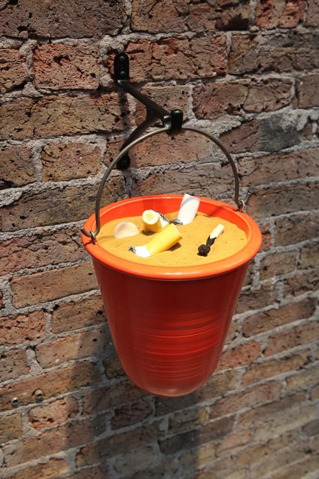 Richard Slee  Fire Bucket, 2016  Ceramic, metal, sand  Bucket 44 x 27 cm diam  Braket 24 x 3 x 20 cm
