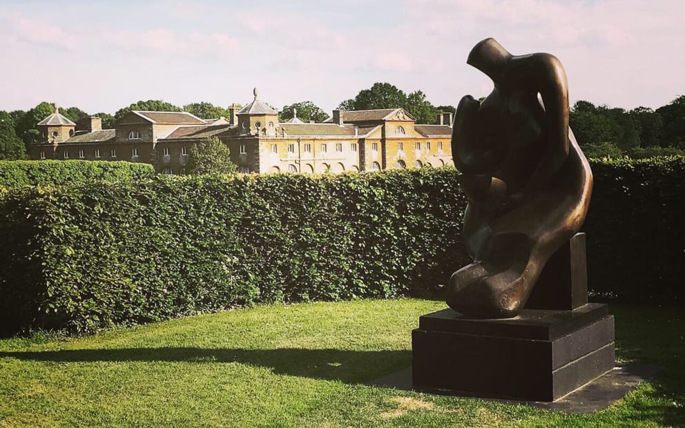 Mother and Child by Henry Moore with our venue - the stables at Houghton Hall in the background