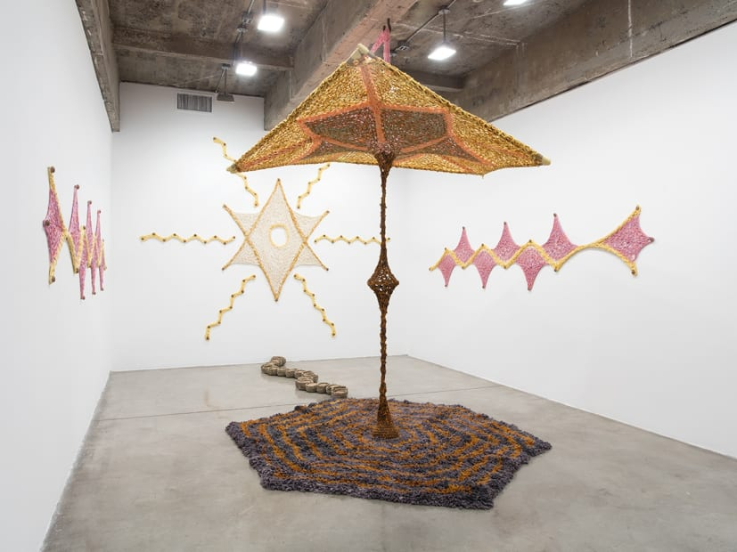 Ernesto Neto installation with crochet in middle of room and crochet on the wall