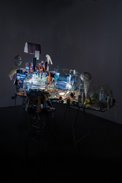 Sarah Sze installation in dark room of video projections on a desk