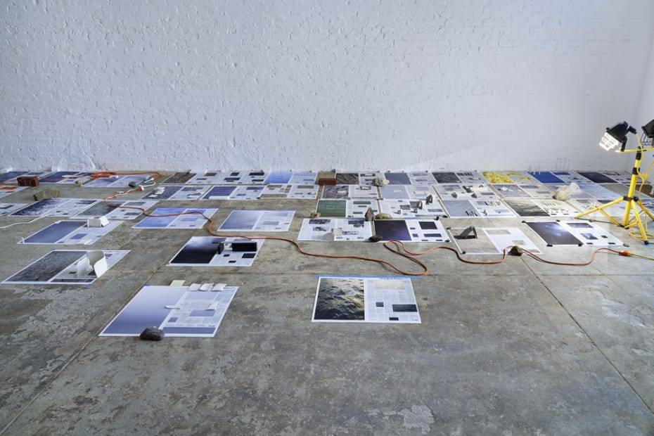 Installation view with newspapers on floor and rocks