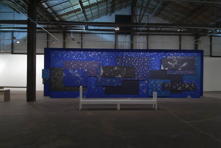image of wall covered in blue paper drawings