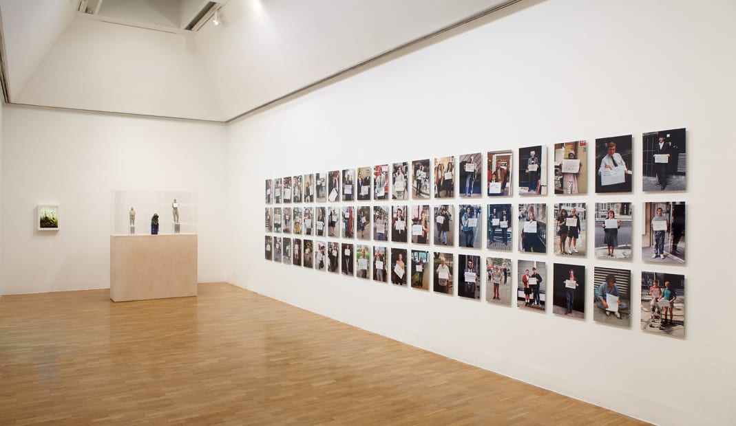 Installation view of Gillian Wearing at Whitechapel Gallery, London, photographs of people holding signs