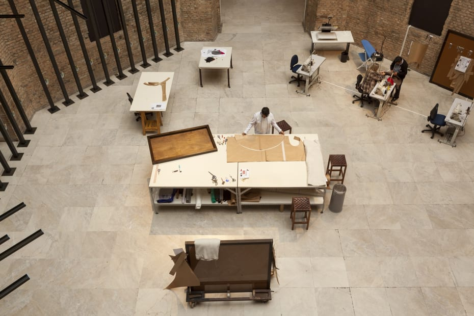 image of tailors sewing / working in a tailor shop set up inside museum, aerial view